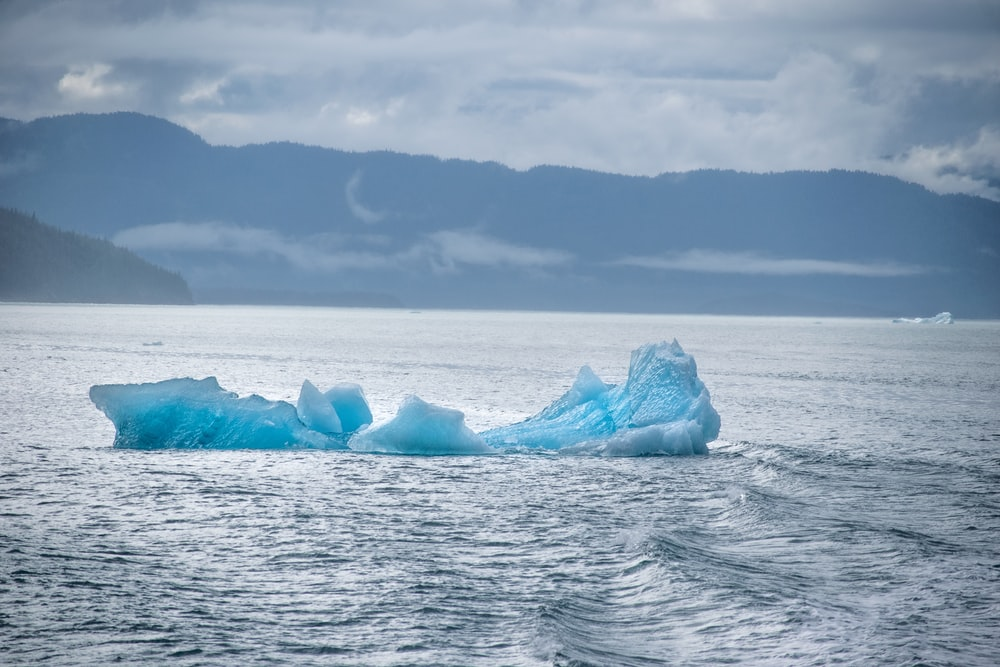 white and blue ice formation on sea viewing mountain during daytime