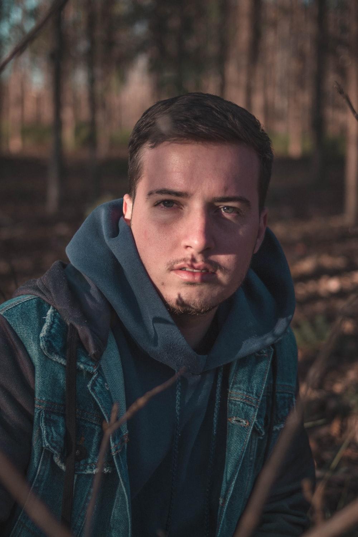 man in blue denim jacket beside trees