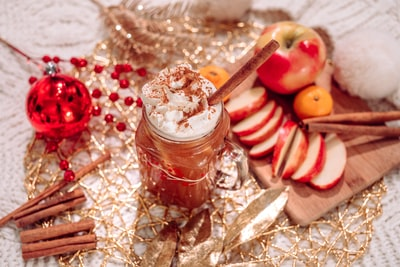 juice with toppings near sliced apple fruits and cinnamon sticks hot cider teams background