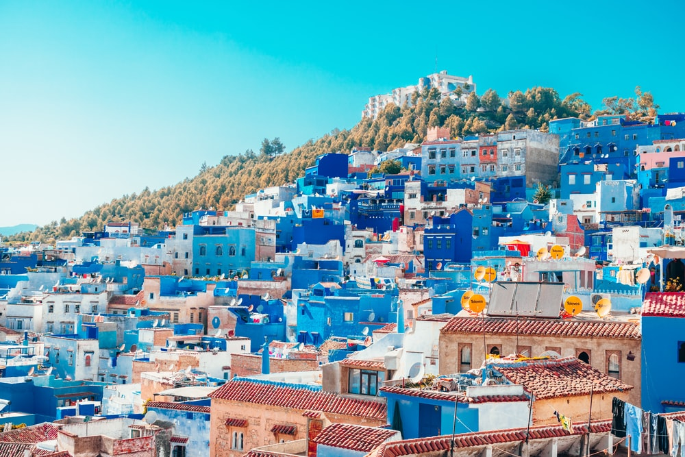 blue and white painted houses on the cliff