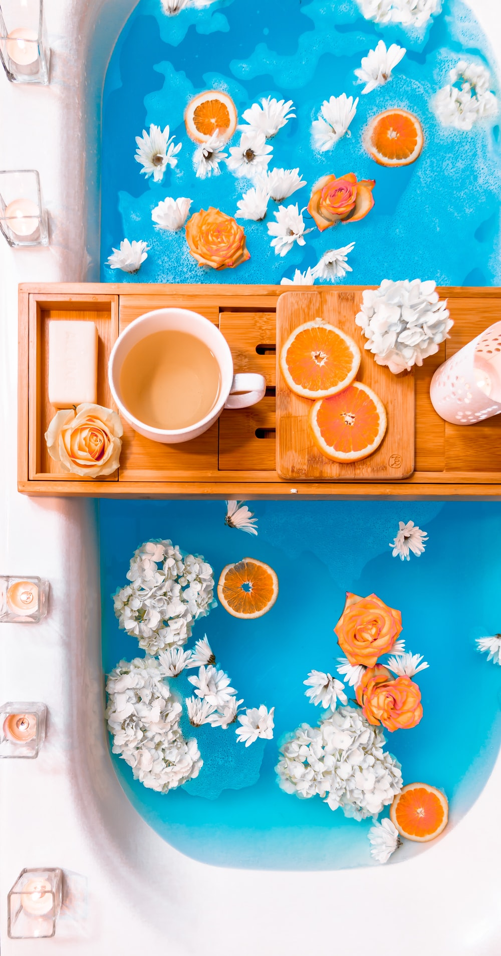 filled mug on brown wooden bathtub tray