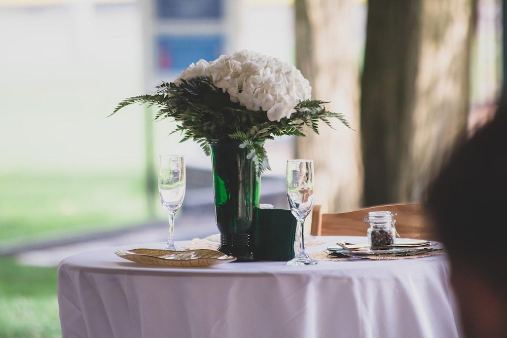 white petaled flowers in green glass vase on table