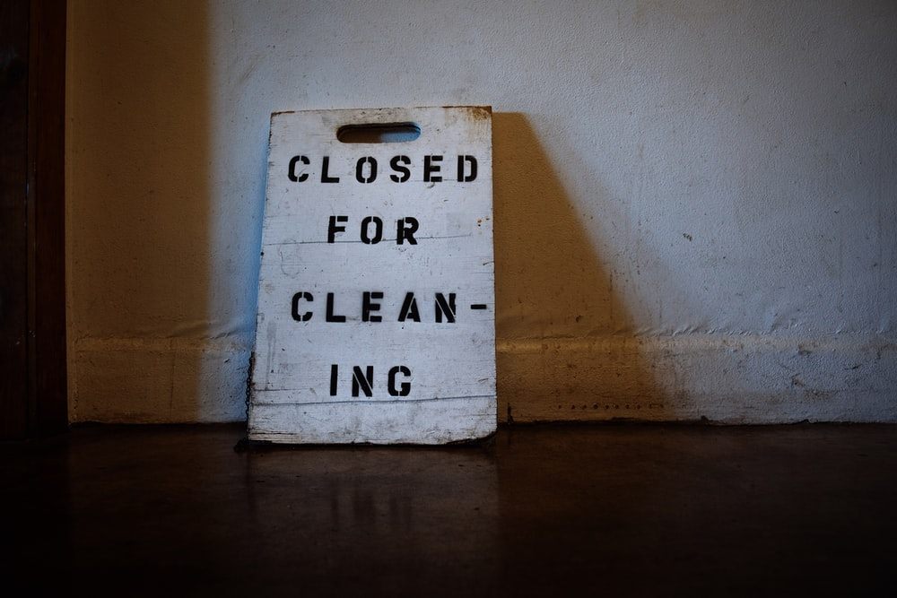 white and black closed for cleaning-printed wooden board signage