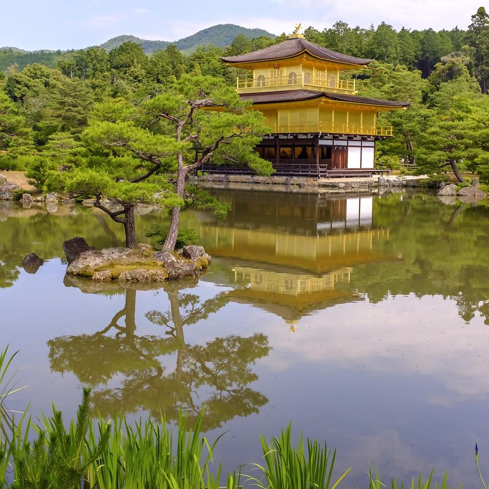 pagoda near tree and lake