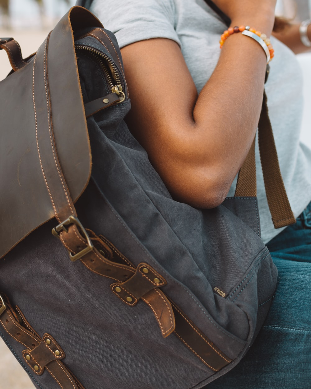 woman wearing gray shirt carrying brown and gray knapsack backpack
