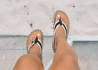 person wearing pair of black-white-and-brown leather flatbed sandals