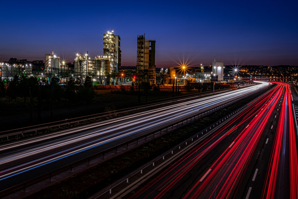 time-lapse photography of passing vehicles in an urban city during nighttime