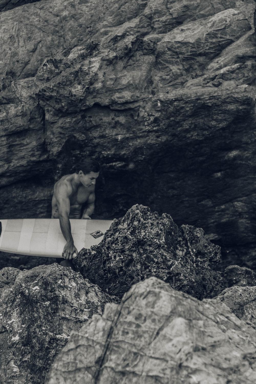 man holding surfboard beside rock