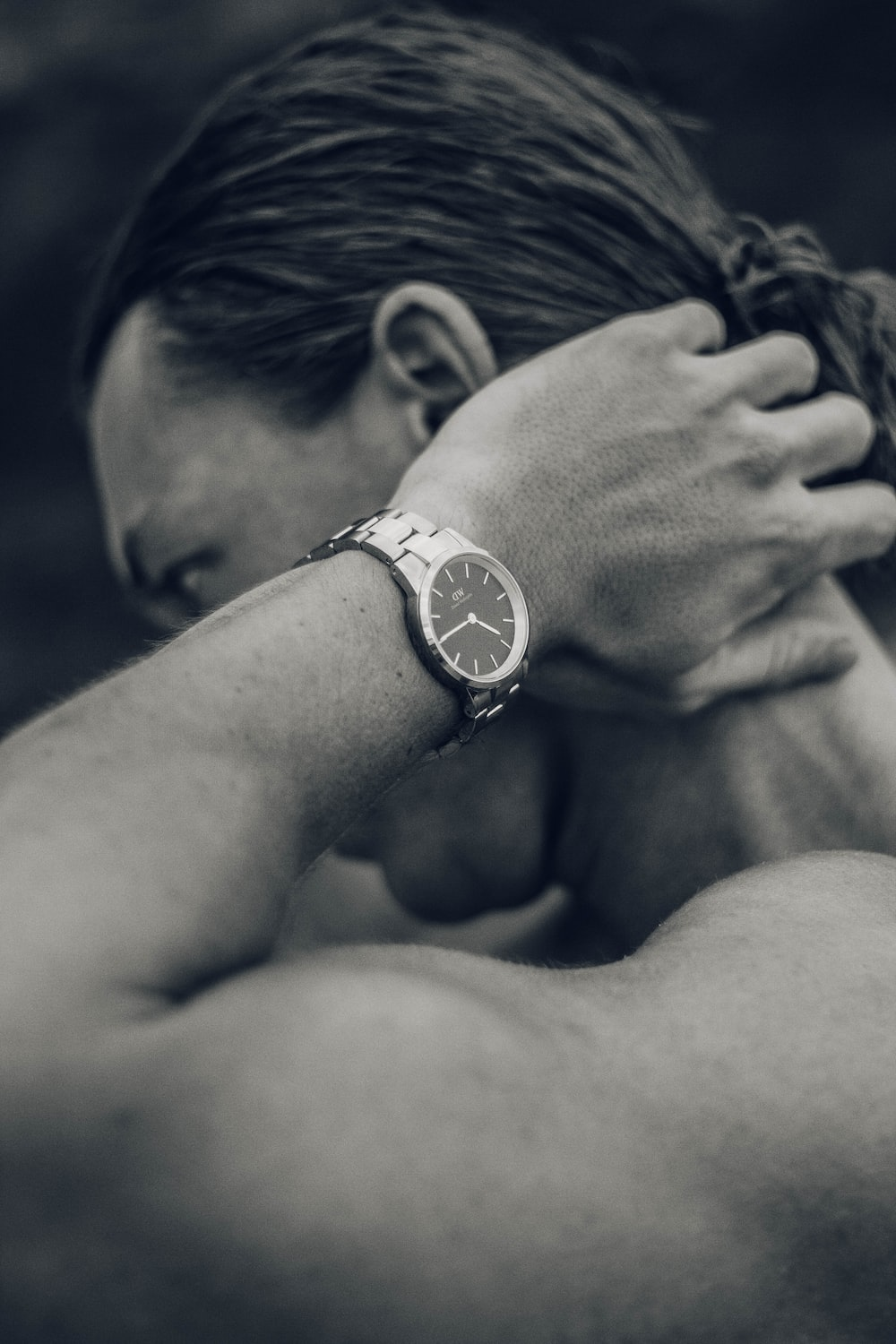 grayscale photography of man touching his nape