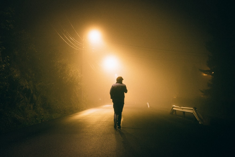 man standing in concrete road during night time