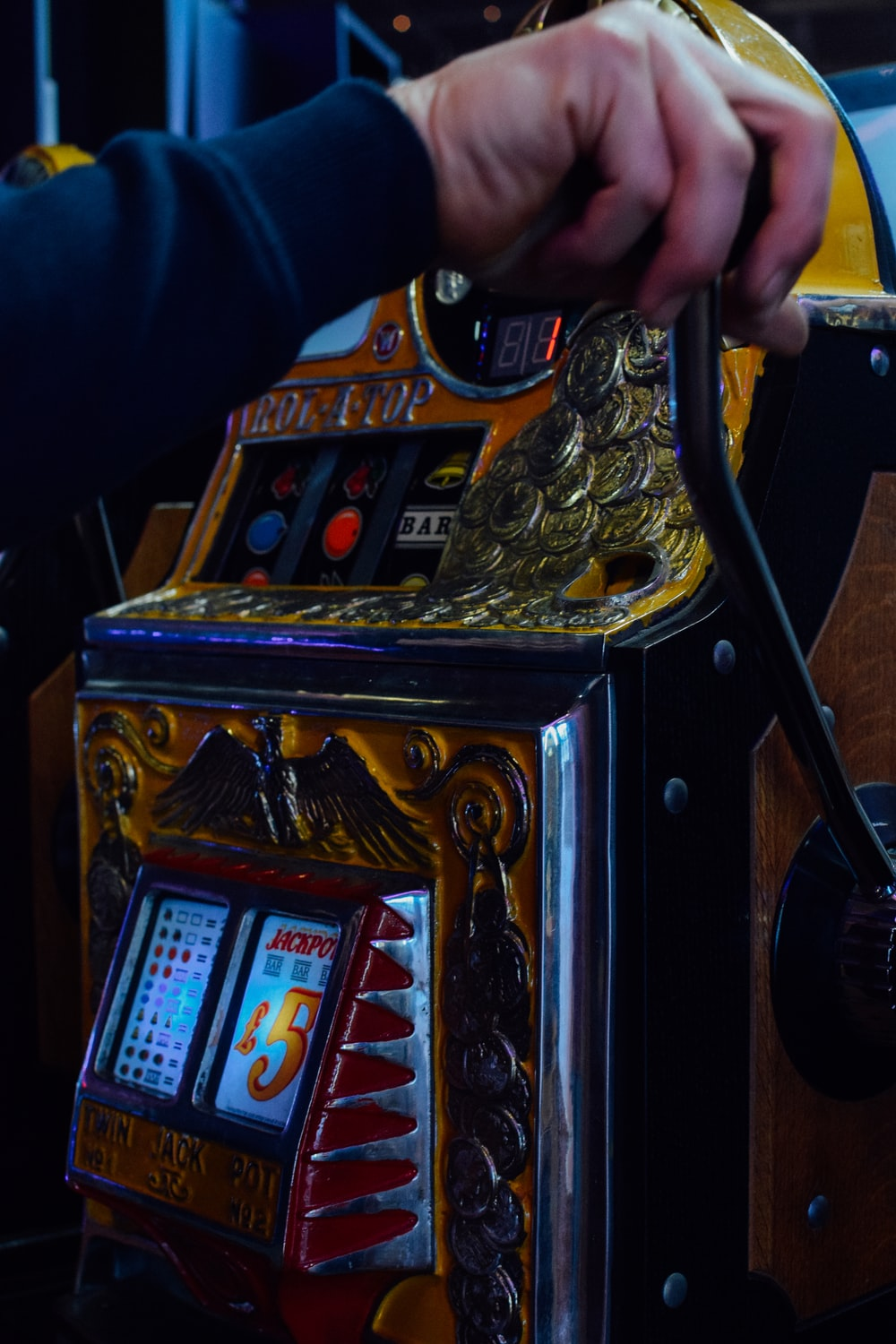 person playing slot machine displaying 5