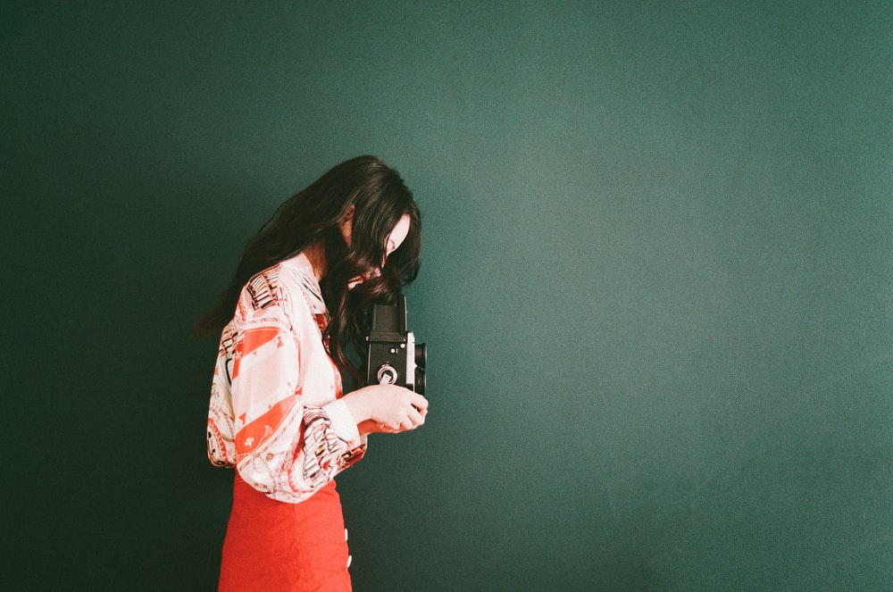 woman holding black camera