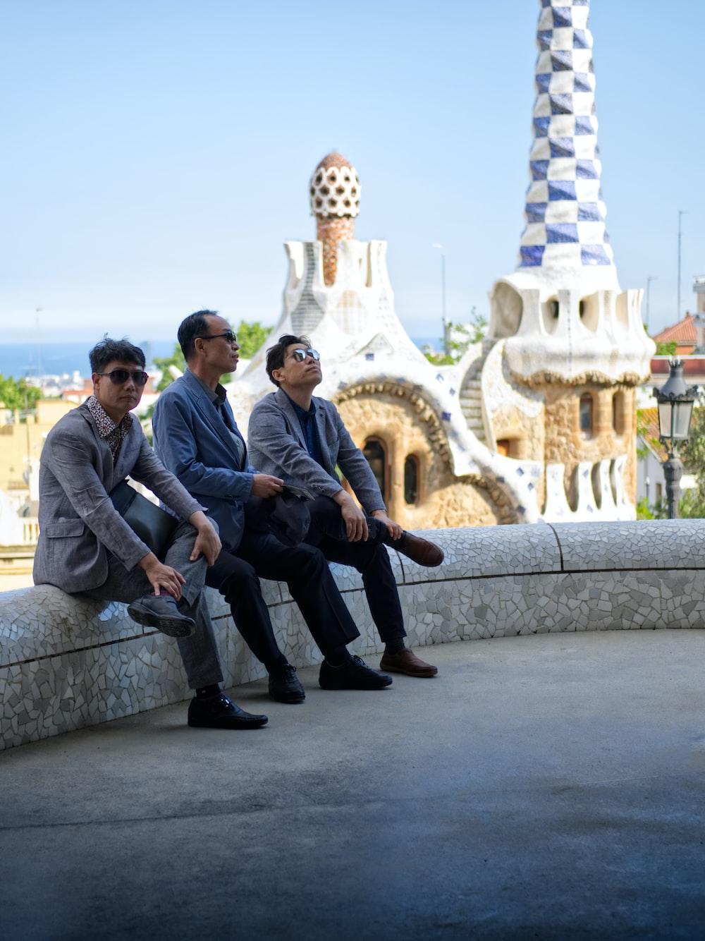 three men sitting on concrete bench
