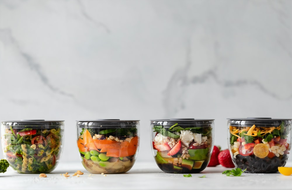 four clear plastic bowls with vegetables