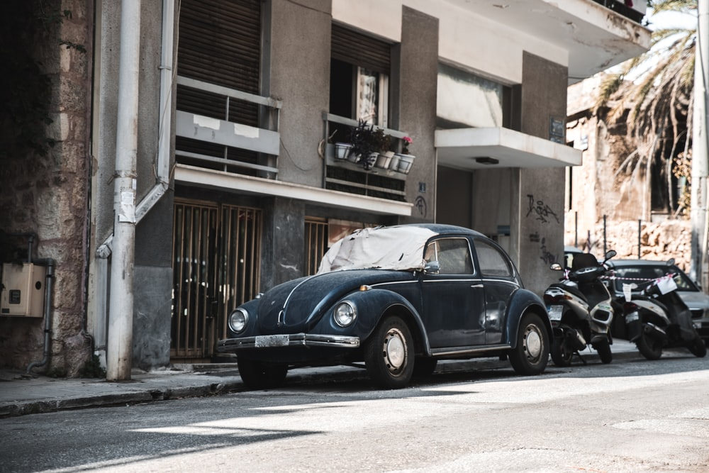 black beetle car parked on sidewalk