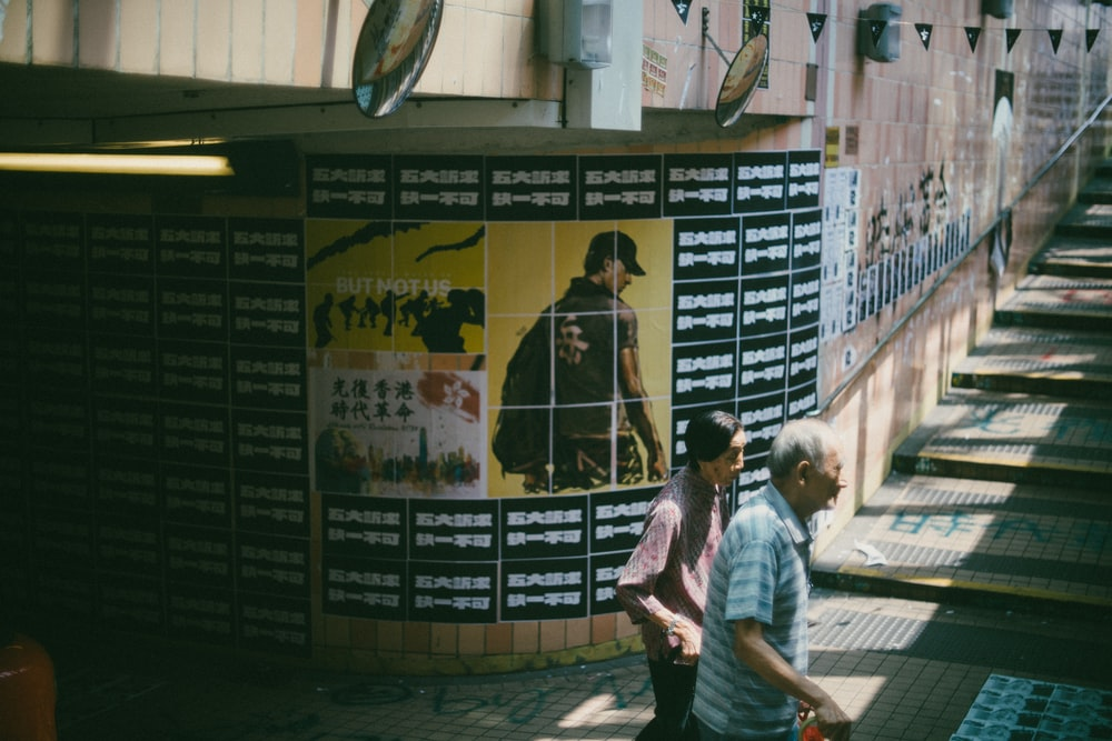 people walking near wall with posters