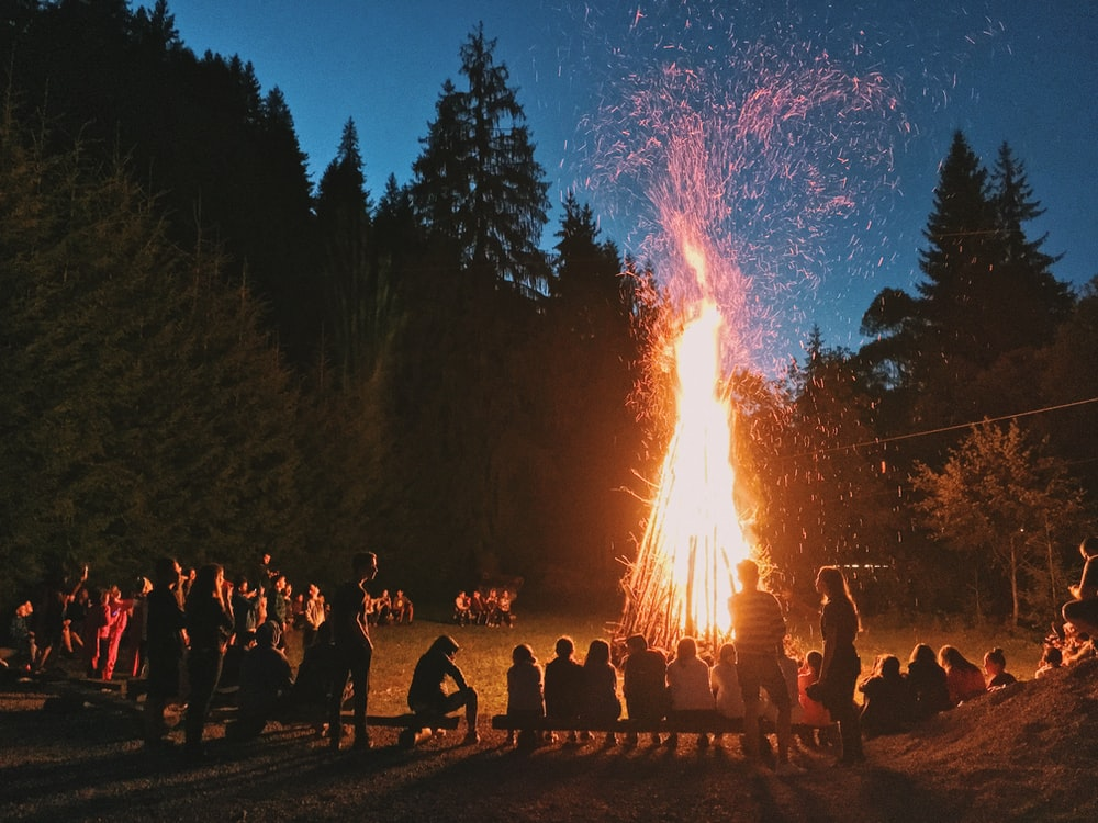 time-lapse photography of a burning bonfire surrounded by people in a camp