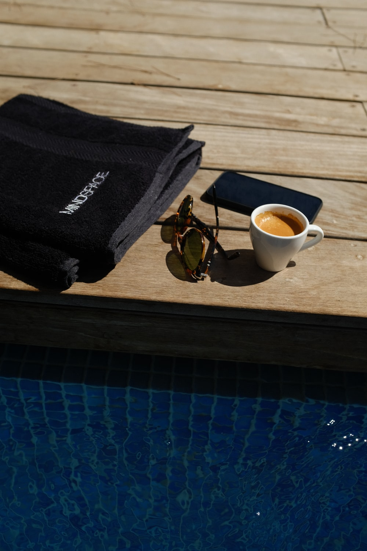 coffee filled mug beside sunglasses