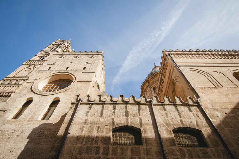 low-angle photography of brown cathedral under a calm blue sky