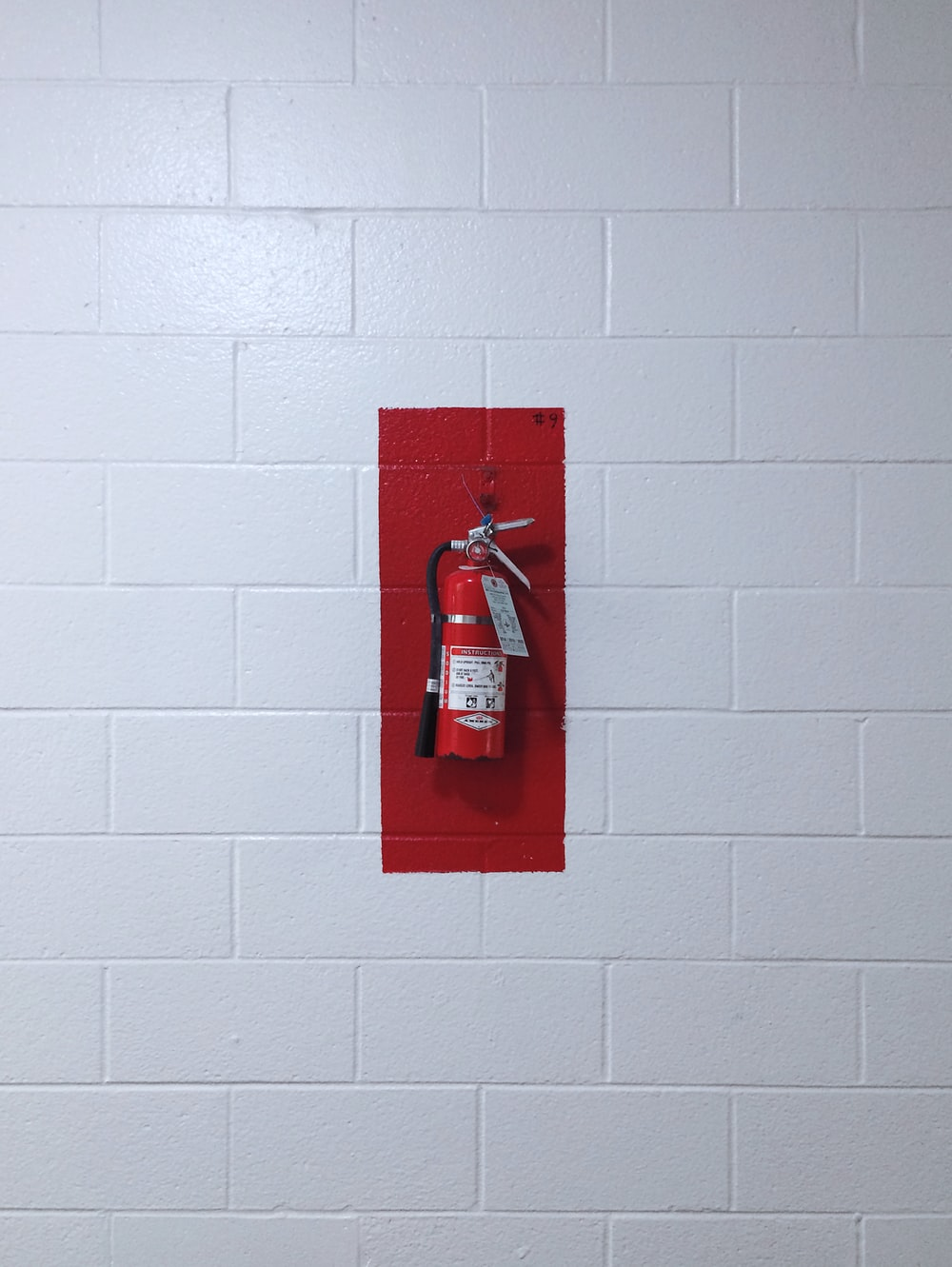 red fire extinguisher on wall