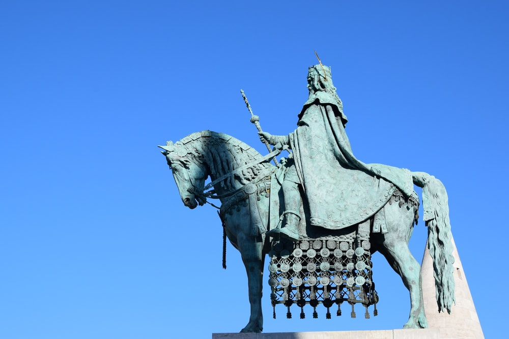 low-angle photography of man riding horse statue under calm blue sky