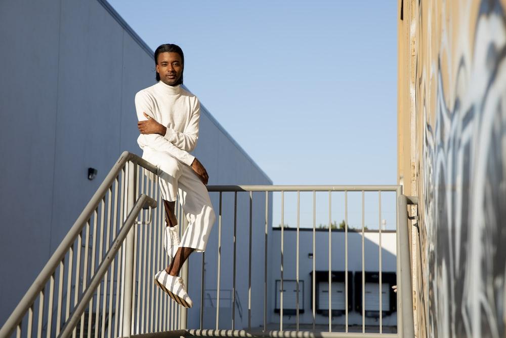 man wearing white long-sleeved shirt sitting on gray stainless steel railings