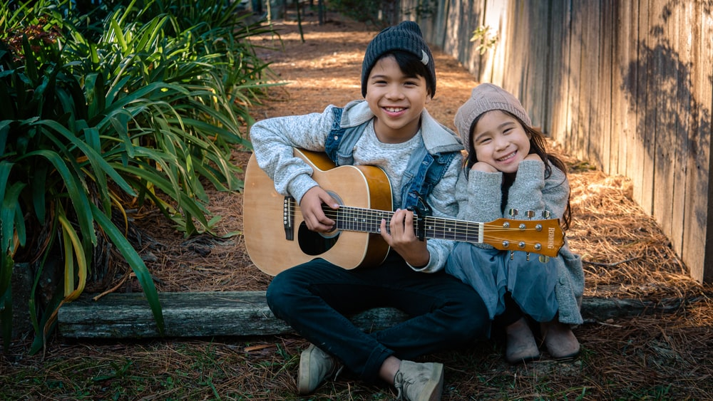 boy holding dreadnought acoustic guitar beside girl during daytime