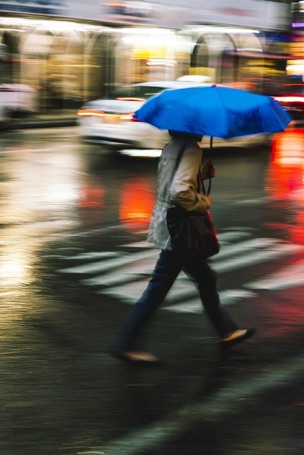 person walking on pedestrian lane while holding umbrella