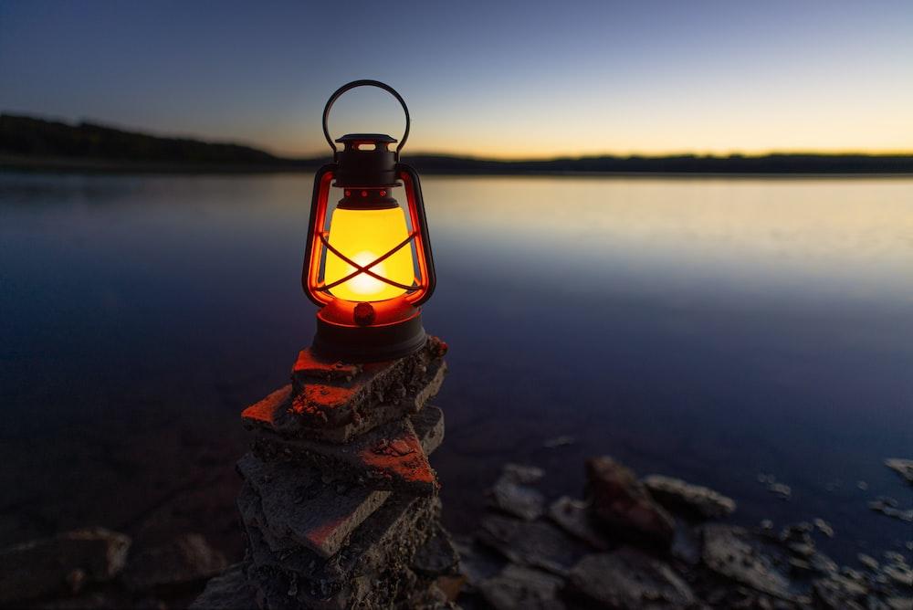 turned-on gas lamp on rock beside sea