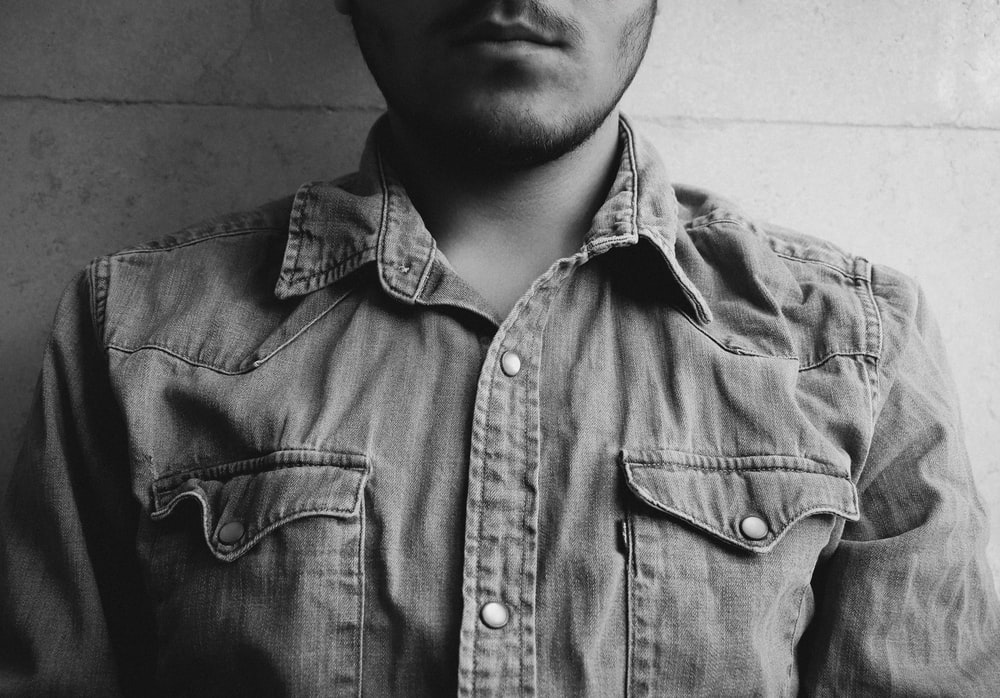 grayscale photography of man wearing gray collared shirt