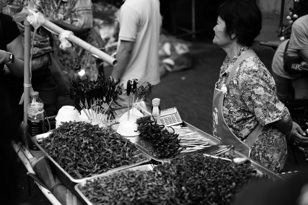 grayscale photo of people near flowers