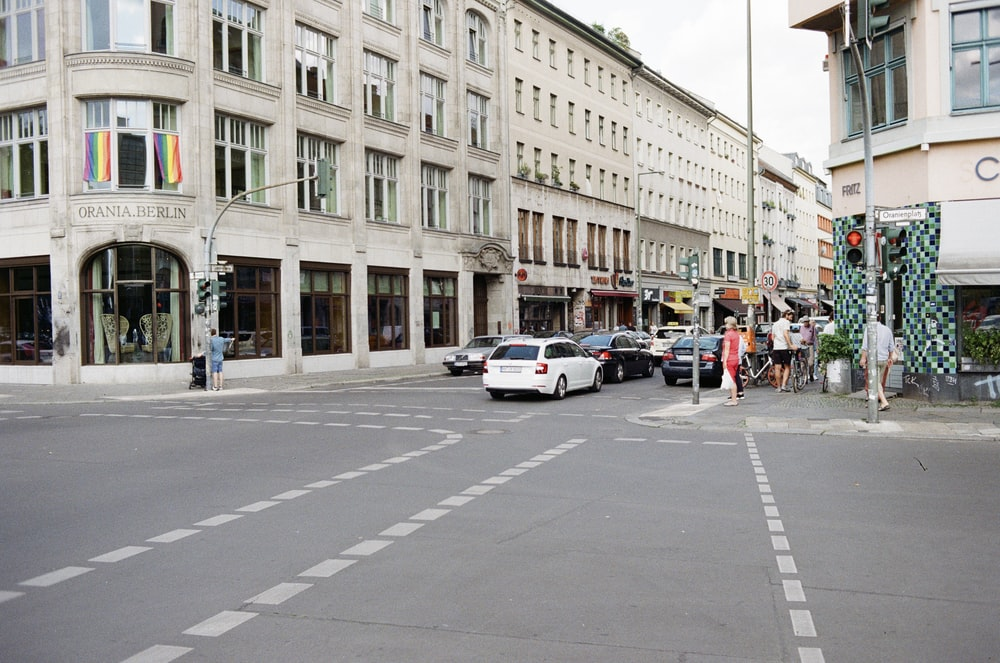 people walking on pathway and vehicles on road beside buildings during daytime