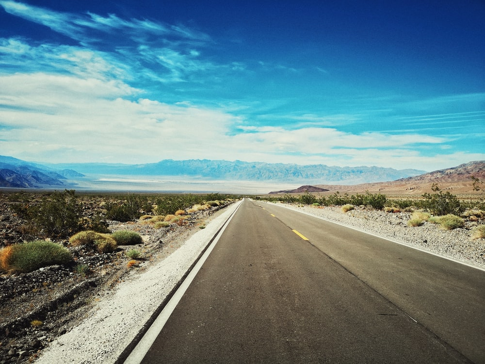 gray concrete road with no vehicle viewing mountain under blue and white skies during daytime