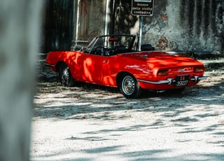 red convertible coupe parked beside building
