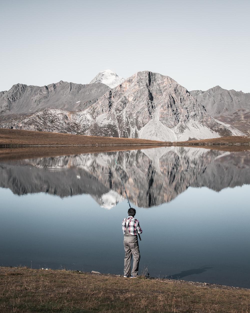 man fishing on calm water at daytime