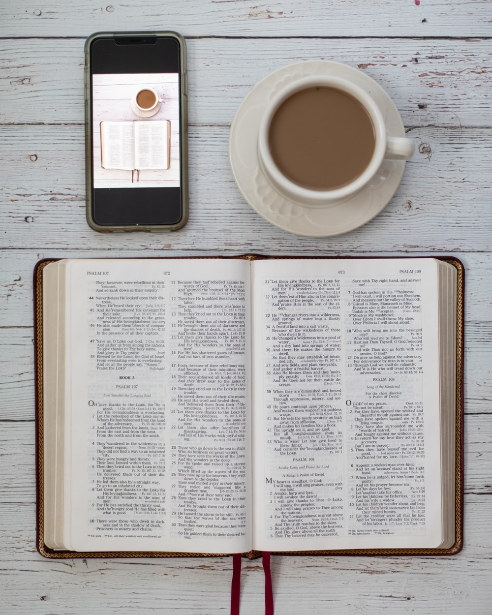 opened bible beside cup of coffee and smartphone on table