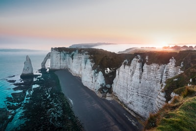 Foggy sunrise at the wonderful white cliffs of Etretat, France.