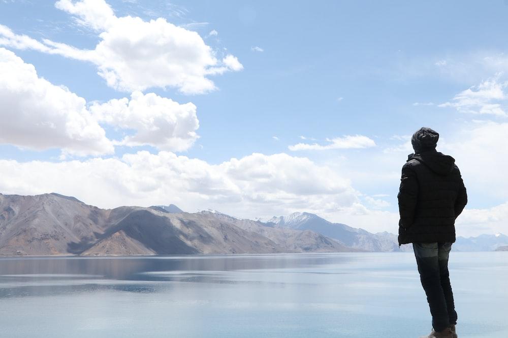 man standing beside water looking towards mountain