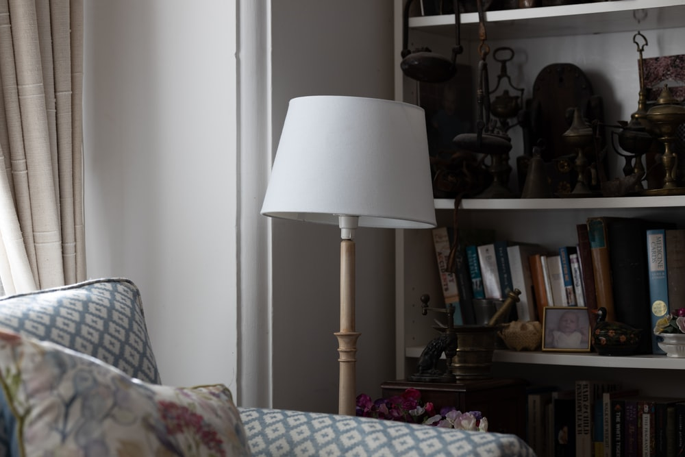 white and beige floor lamp near book shelf and blue and white sofa chair