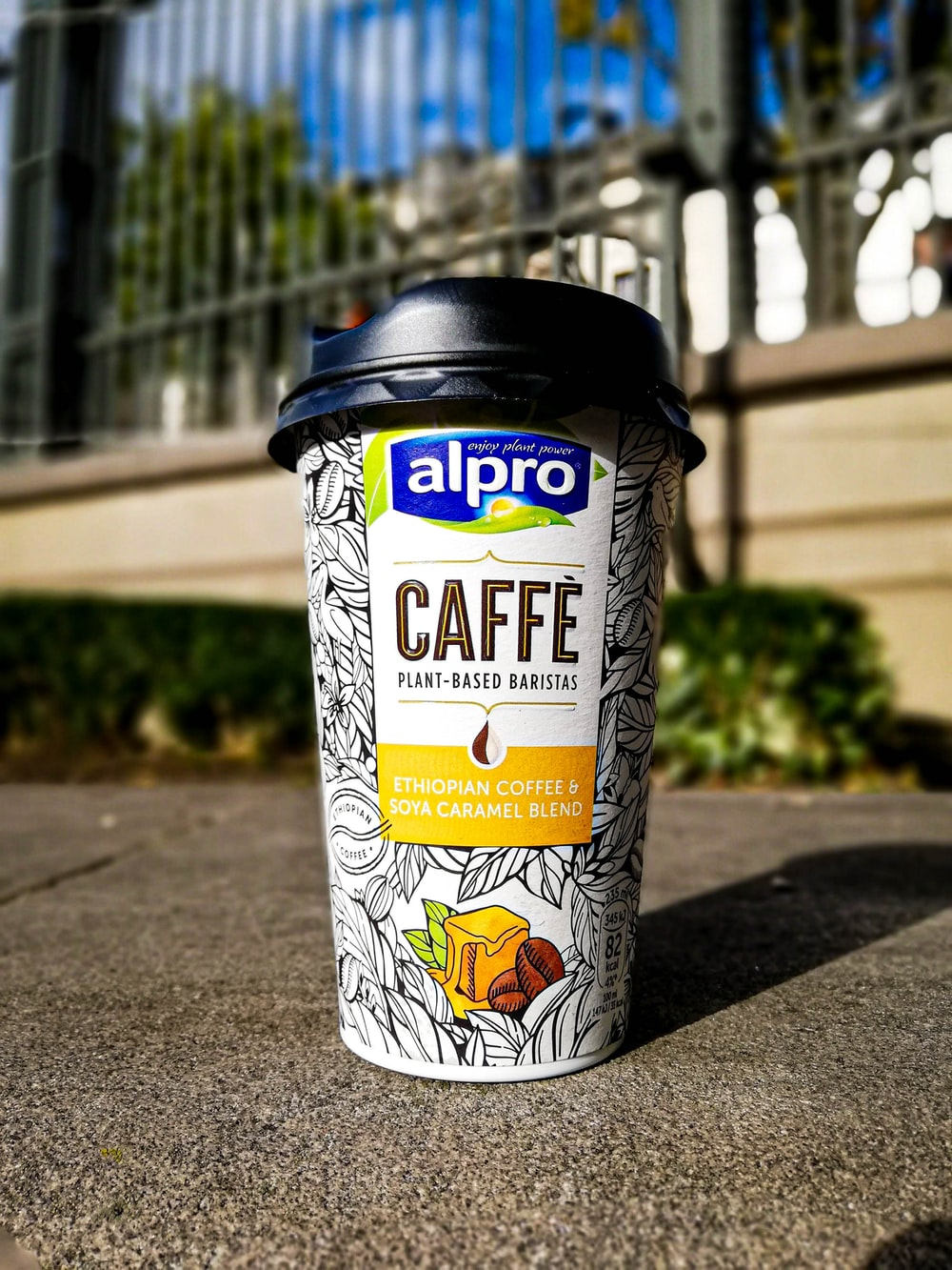 Alpro caffee coffee cup with lid on concrete pavement