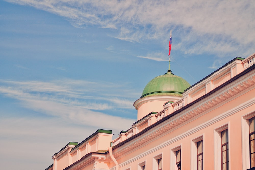 pink and green dome building under blue and white skies during daytime