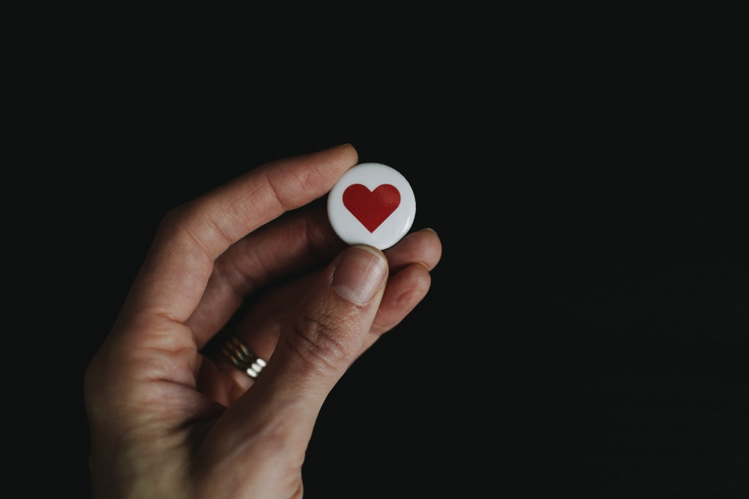 Hand holding a button pin with a heart on it