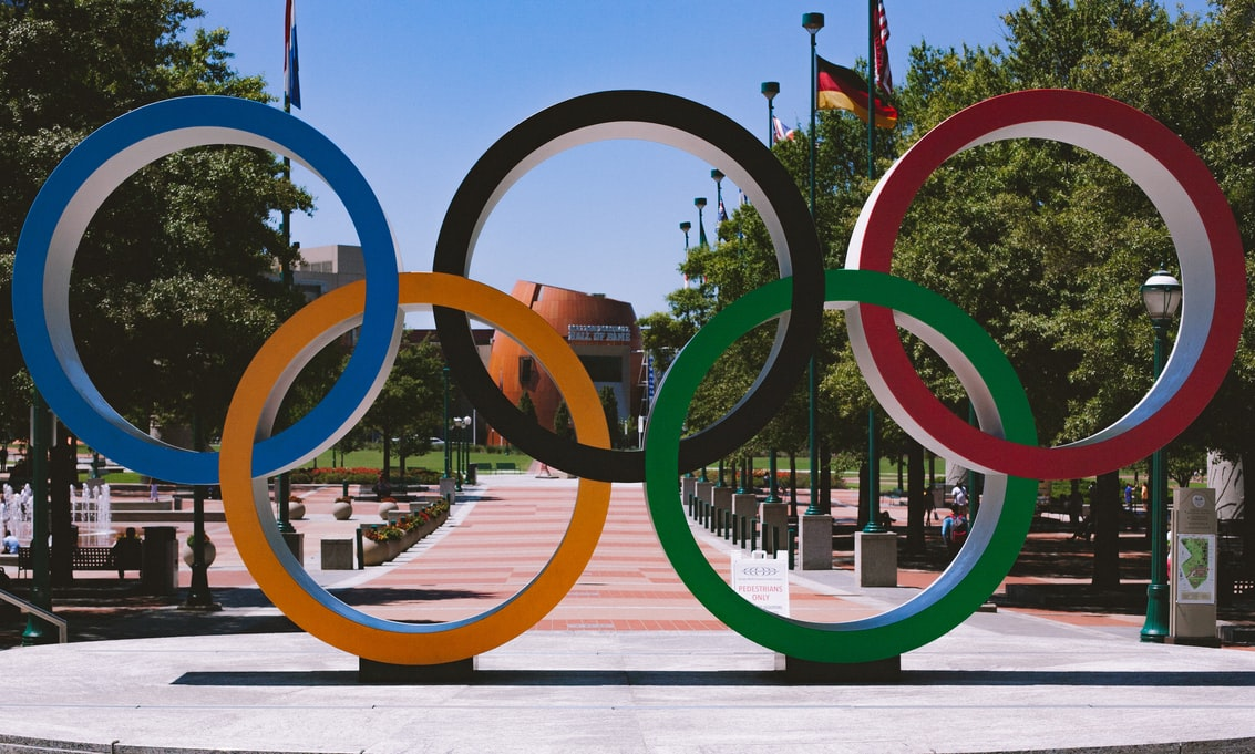 The Olympic flag's colors are always red, black, blue, green and yellow rings on a field of white. This is because at least one of those colors appears on the flag of every nation on the planet.