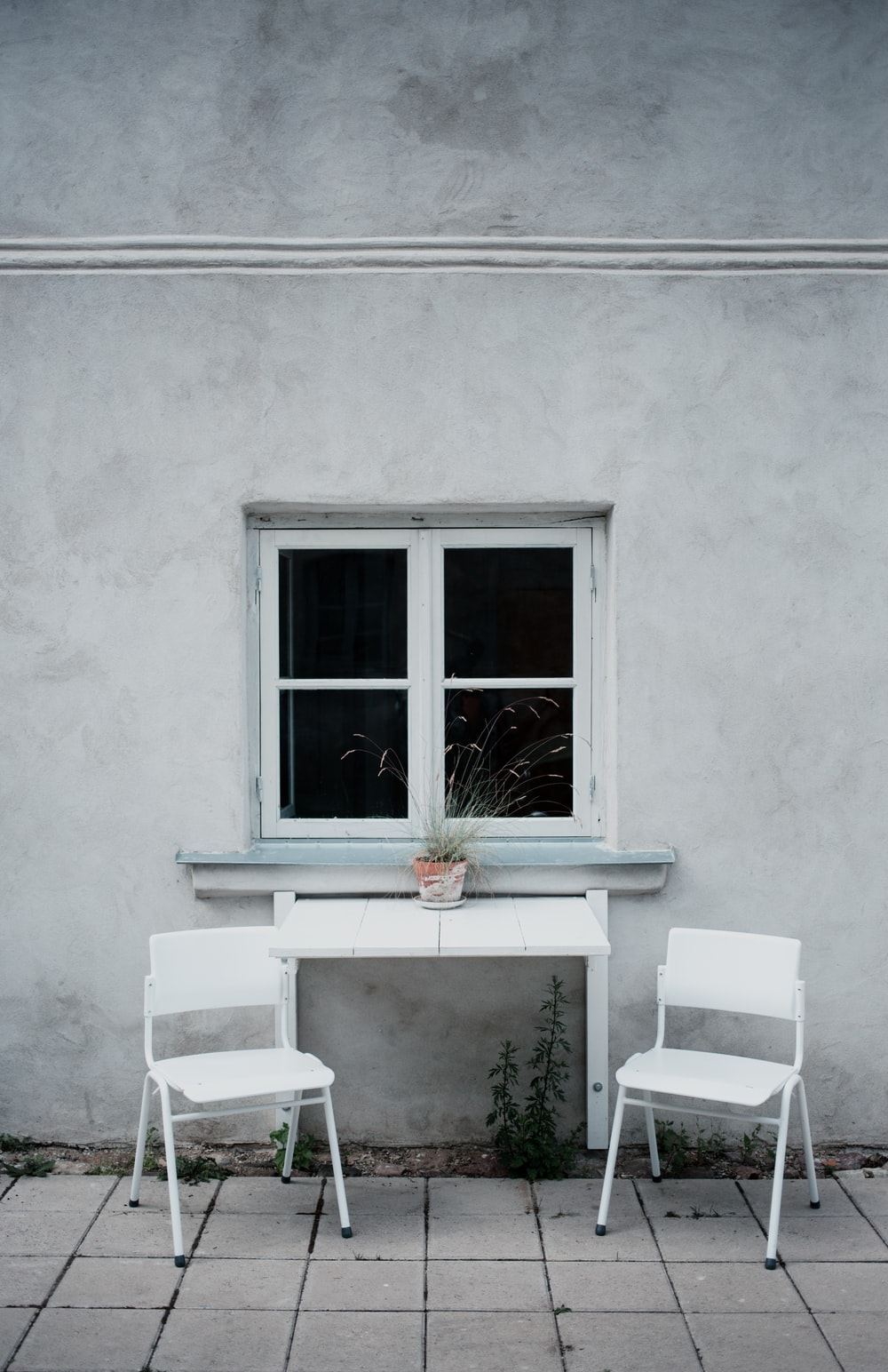 two white folding chairs beside wall