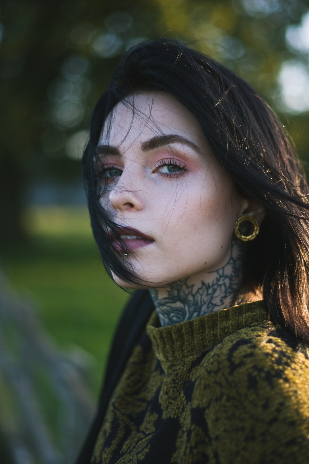woman in floral sweater with neck tattoo and purple lipstick