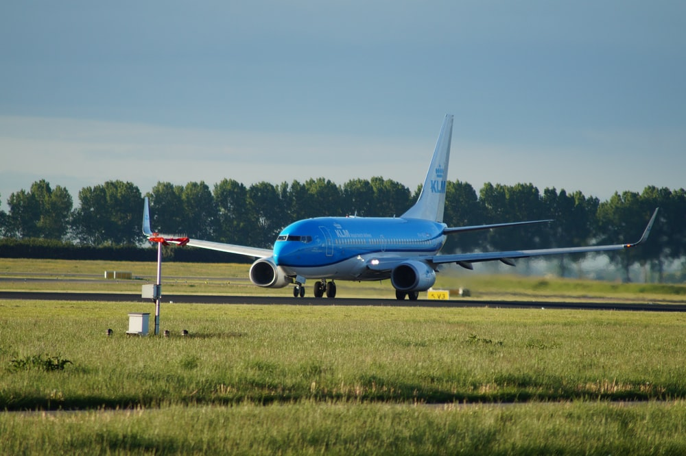 blue airplane on airfield during day