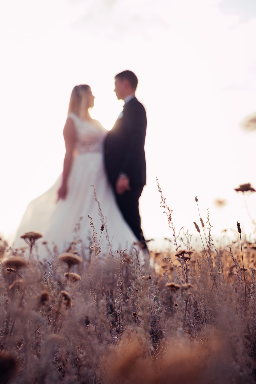 bride and groom standing on field