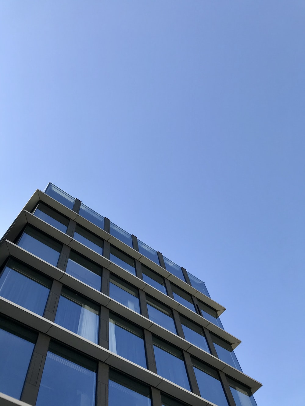 low-angle photography of blue glass walled building