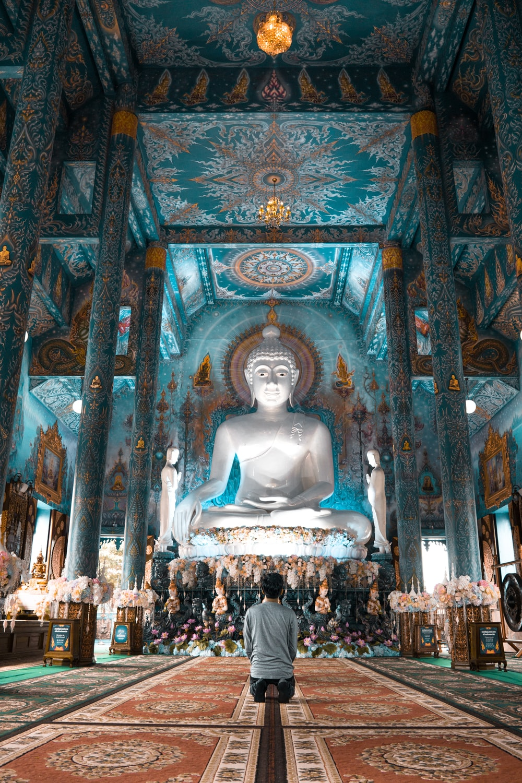 person kneels near Buddha