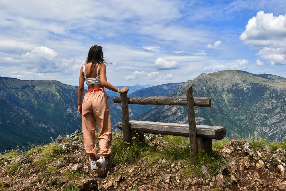 woman standing near wooden bench viewing mountain under blue and white skies during daytime
